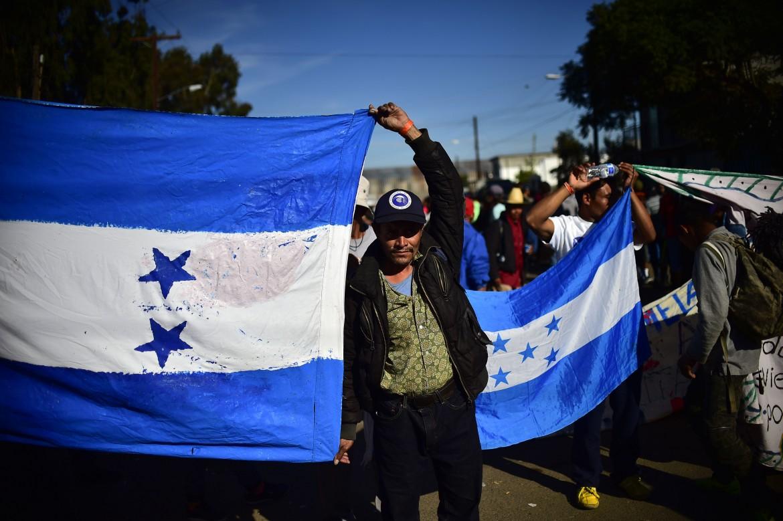 Bandiere dell'Honduras in marcia con la carovana migrante presso il valico di El Chaparral, tra Usa e Messico