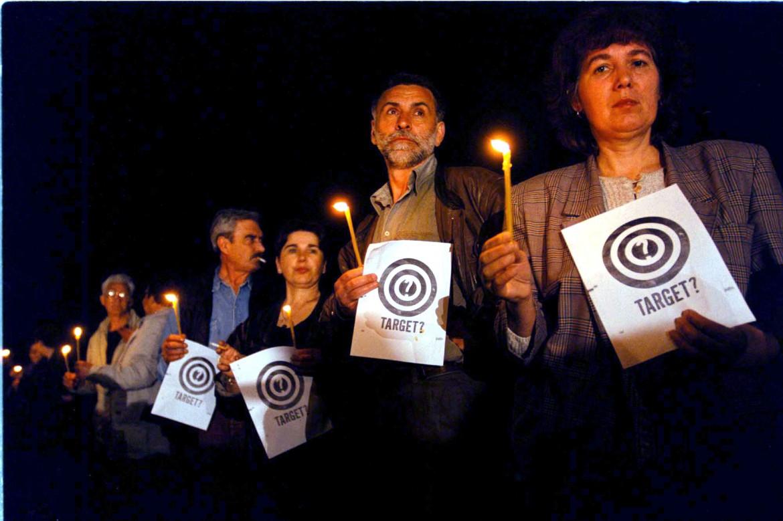 I cittadini di Belgrado con il simbolo del «target» per fermare il bombardamento dei ponti. Sotto, Massimo Cacciari