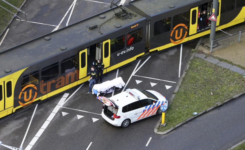 Utrecht, il tram della sparatoria e il corpo di una vittima a terra; sotto la polizia circonda la zona