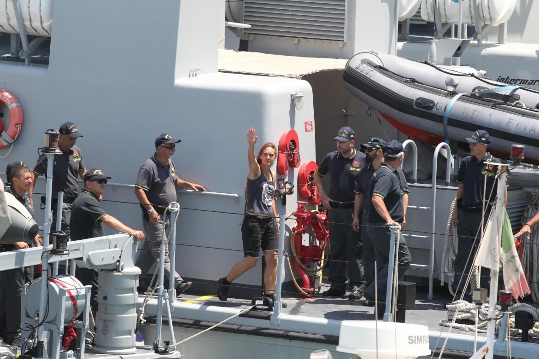 Carola Rackete arriva a Porto Empedocle sulla motovedetta della finanza; in basso solidarietà alla capitana davanti al tribunale di Agrigento