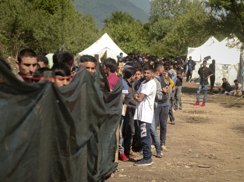 Migranti in fila in un campo profughi in Bosnia