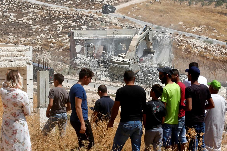 Un bulldozer al lavoro sotto lo sguardo dei palestinesi