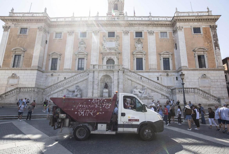 Protesta in piazza del Campidoglio per l'emergenza rifiuti a Roma; in basso Virginia Raggi e Nicola Zingaretti