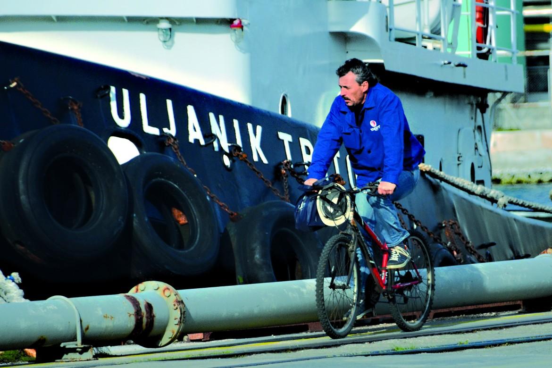 Operaio in bici davanti a un battello ancorato alla banchina del cantiere di Pola per manutenzione