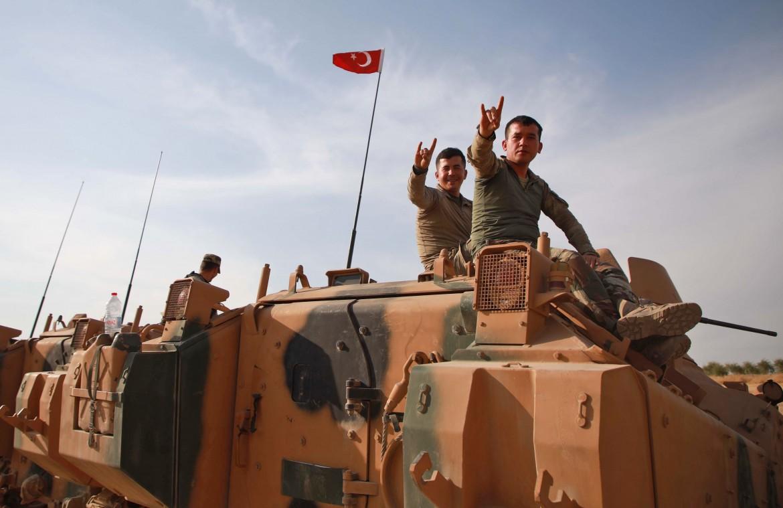 Soldati turchi fanno il simbolo dei lupi grigi, gruppo nazionalista di destra mentre attraversano il villaggio di Qirata, alla periferia di Manbij