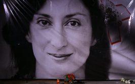 Fiori e candele in omaggio alla giornalista maltese Daphne Caruana Galizia durante una veglia davanti al tribunale della Valletta in basso Corinne Vella