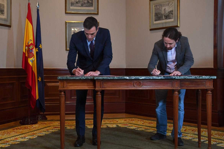 Pedro Sánchez e Pablo Iglesias firmano il pre-accordo di governo; in basso Pablo Simón Cosano