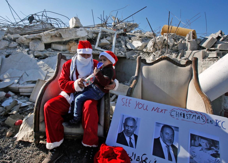 Un Babbo Natale palestinese sulle macerie di una casa demolita nel villaggio di al-Khader