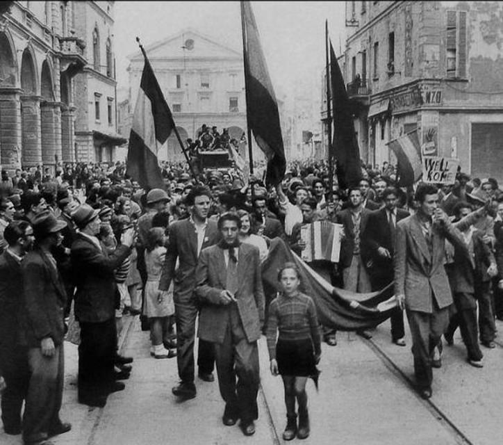 Partigiani sfilano nella città in festa il giorno della Liberazione