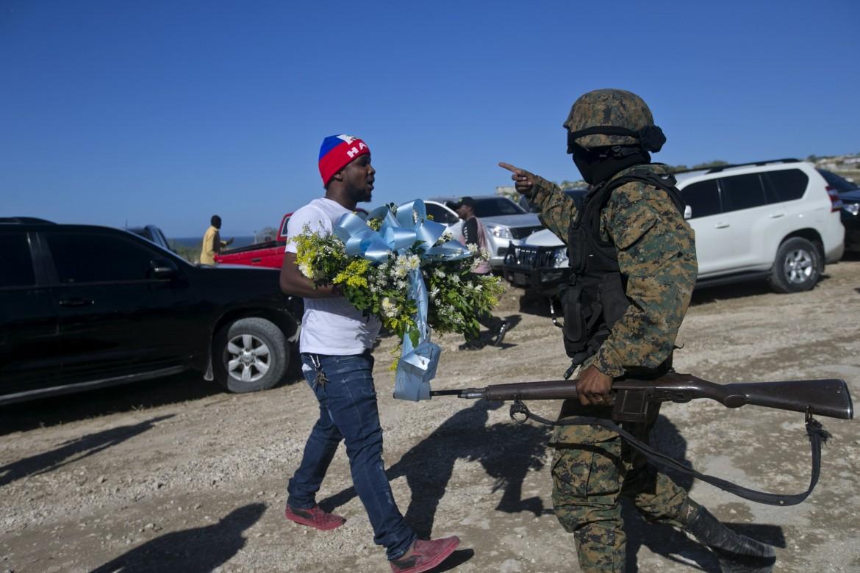 Haiti, 12 gennaio. Un uomo tenta invano di deporre una corona di fiori a Titanyen, la collina dove sono sepolti i morti senza nome del terremoto 2010