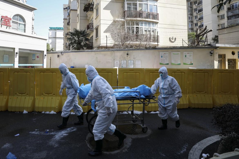 Il personale medici di Wuhan trasporta il corpo di una vittima del virus