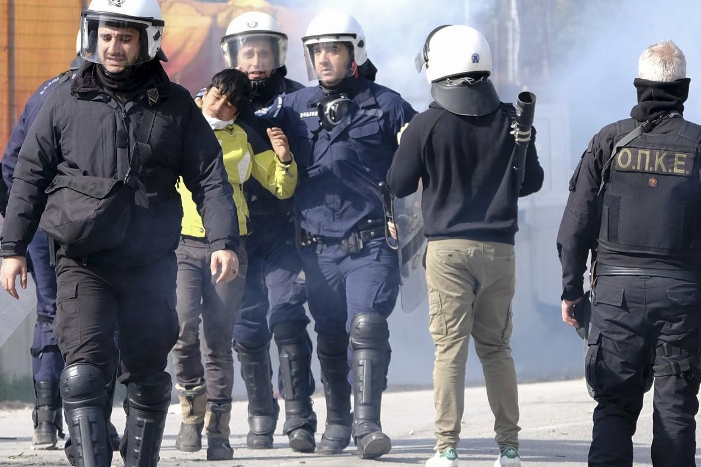 Poliziotti anti-sommossa greci arrestano un giovane migrante nel campo di Moria, Lesbo