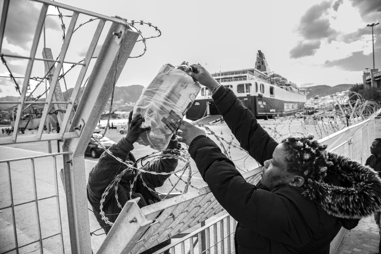 Due donne si scambiano delle masserizie attraverso la barriera del porto di Lesbo