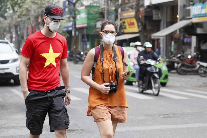 Con la mascherina per le strade di Hanoi