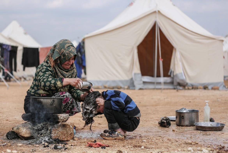 Una donna siriana lava il figlio in un campo profughi improvvisato a Ma'arrat Misrin, nel nord della Siria