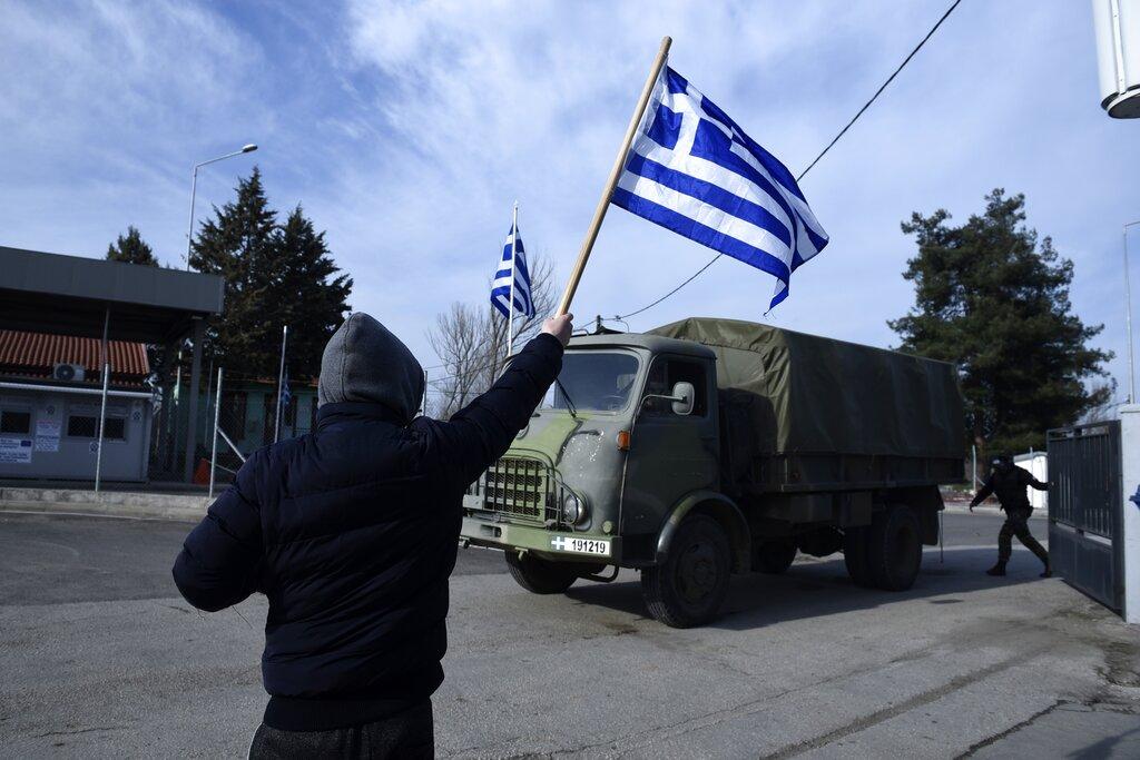 Uomo sventola bandiera greca davanti a un convoglio militare. Frontiera greco-turca di Kastanies, 01/03/2020 (foto di Giannis Papanikos)