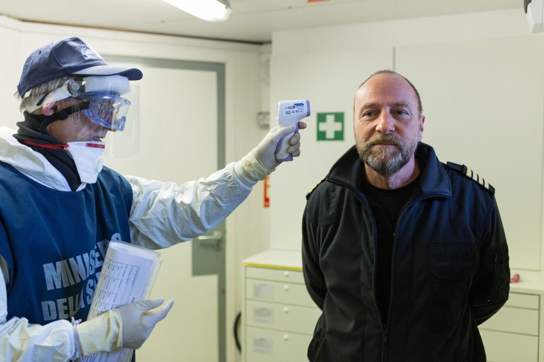 Un medico del ministero della Salute controlla la temperatura corporea al capitano della Sea Watch 3