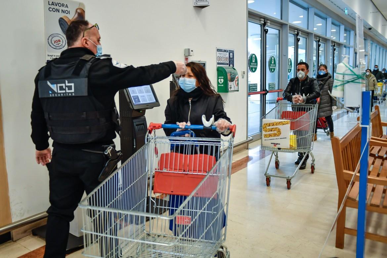 Il controllo della temperatura da parte di un vigilante all'ingresso di un supermercato