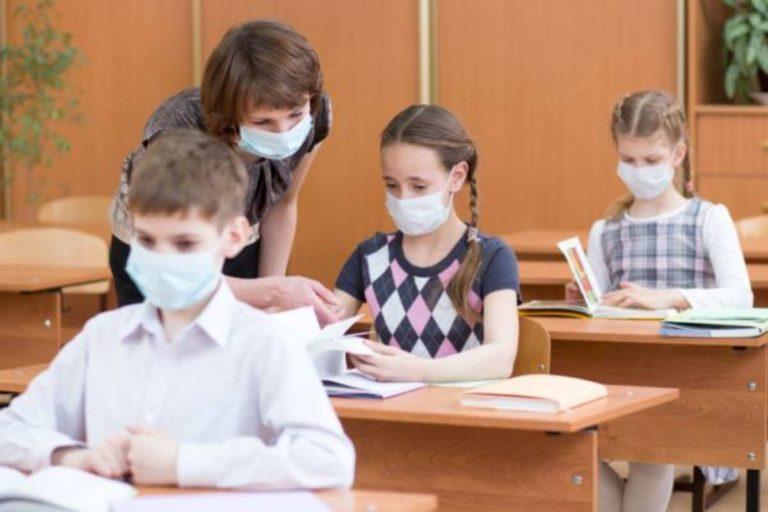 Bambini e insegnanti di scuola primaria con la mascherina in classe