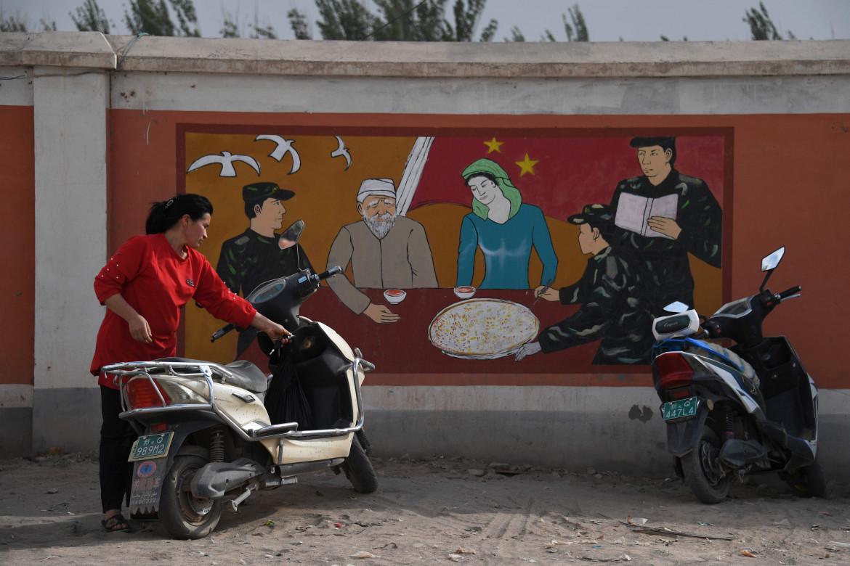 Un murale di propaganda cinese nella regione dello Xinjiang