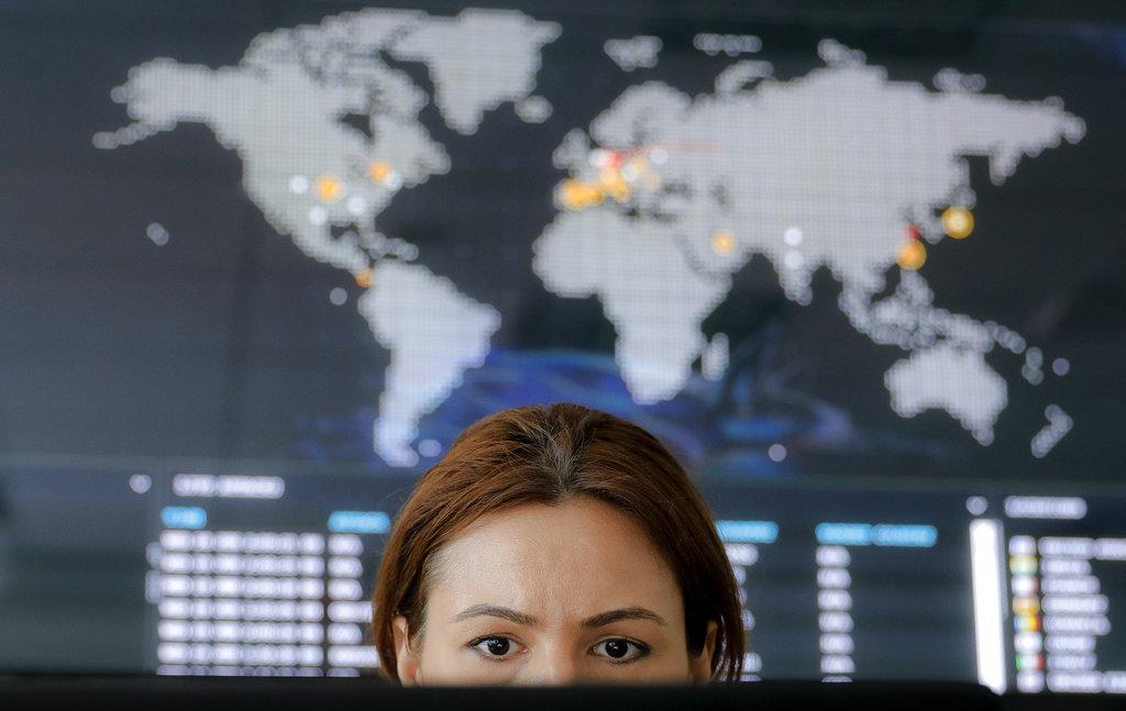 Una donna guarda lo schermo di un pc, sullo sfondo la mappa in tempo reale di un attacco cibernetico globale