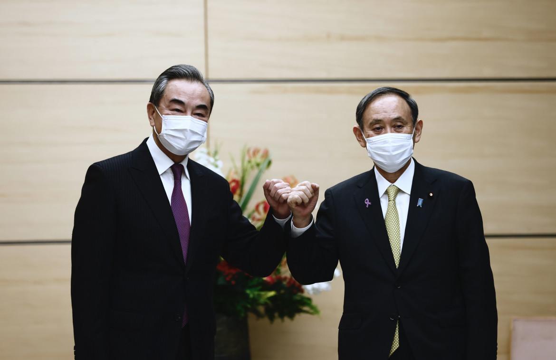 Primo ministro giapponese Suga e il ministro degli esteri cinese Wan Yi
