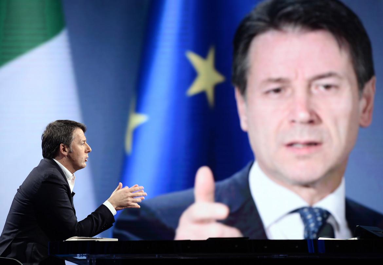Renzi a un dibattito televisivo. Sullo sfondo Conte.