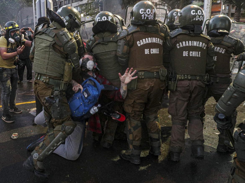 I carabineros arrestano un manifestante nel centro di Santiago