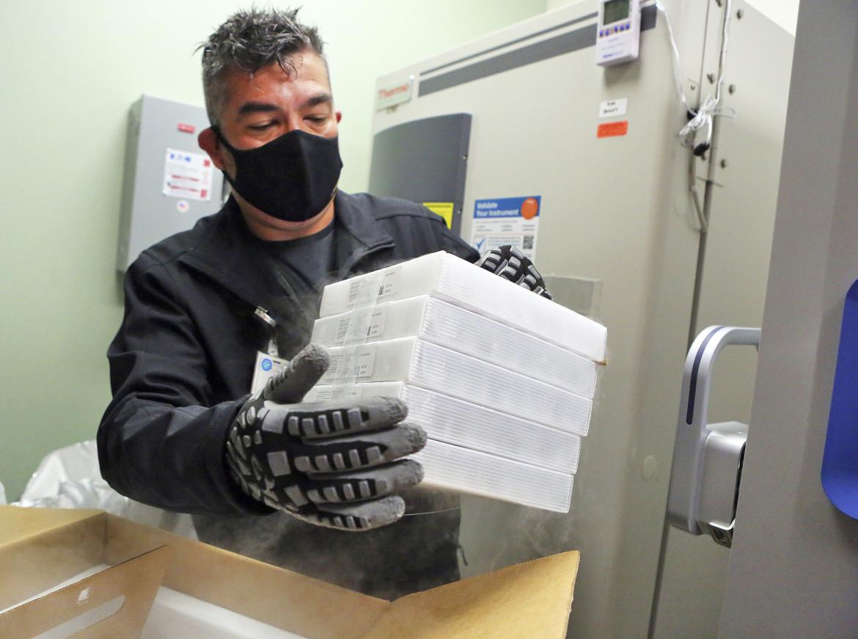 Un addetto maneggia una scatola di vaccini Pfizer-BioNTech