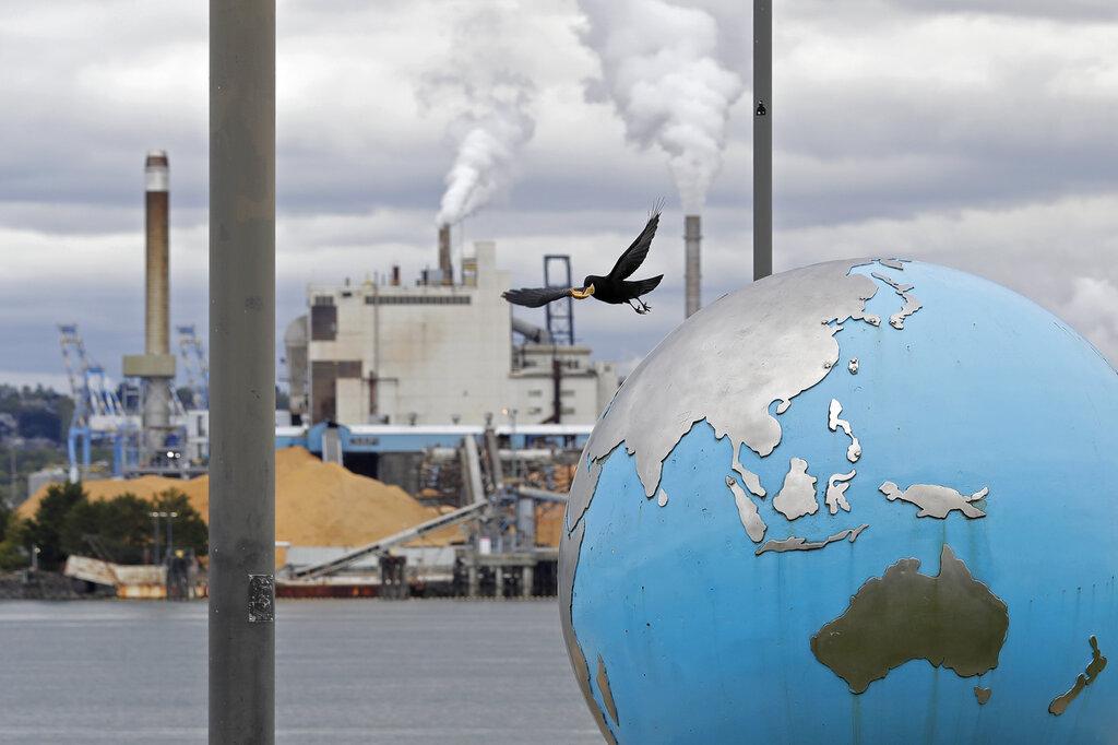 Scultura della Terra, sullo sfondo una fabbrica inquinante