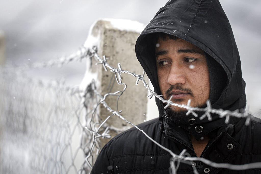 Un uomo vicino alla recinzione del campo di Lipa, in Bosnia