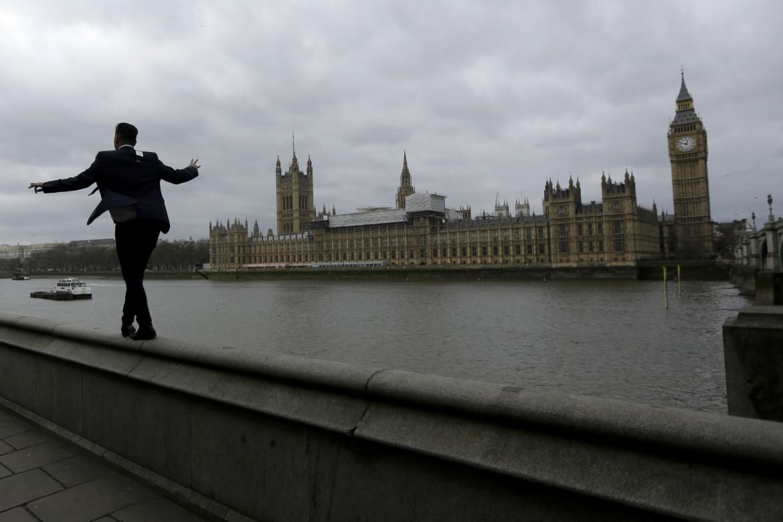 In bilico sull'argine del Tamigi; in basso Boris Johnson, David Cameron, Nigel Farage e Theresa May