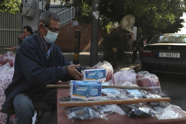 Venditore di mascherina a Beirut, in basso folla in un supermarket