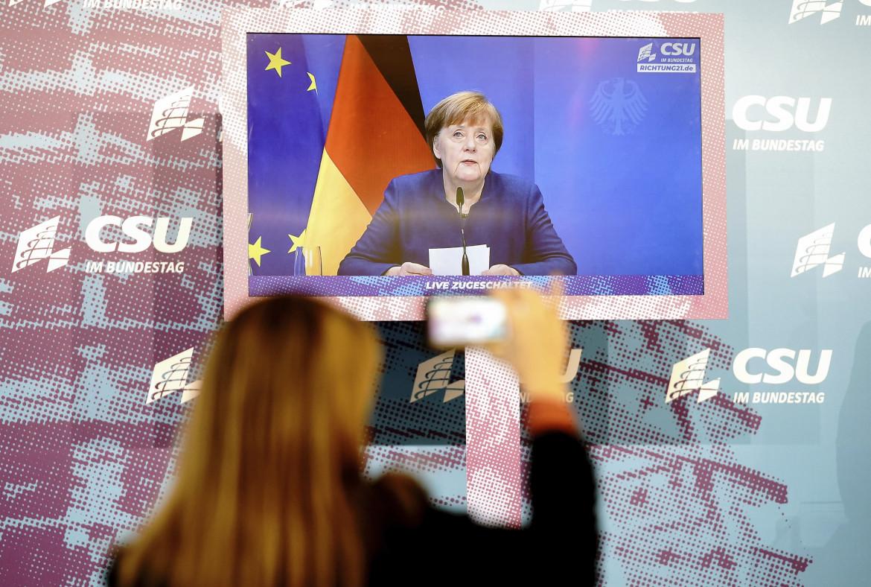 Berlino, intervento in tv di Angela Merkel; in basso Friedrich Merz