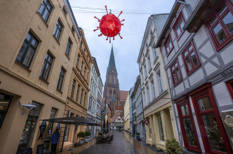 Decorazione a forma di coronavirus davanti alla cattedrale di Schwerin, in Germania. In basso Angela Merkel