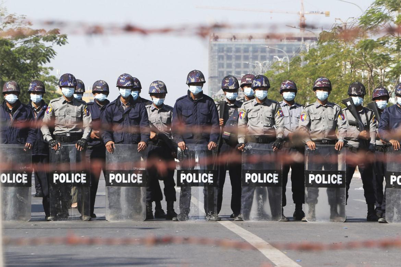 Poliziotti a Mandalay, Myanmar, presidiano una strada bloccata dai manifestanti durante una protesta contro il golpe militare