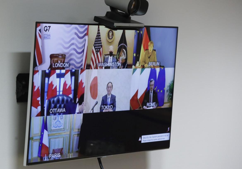 Sullo schermo le scrivanie dei leader del G7: l'americano Biden, la tedesca Merkel, il giapponese Suga e l'italiano Draghi