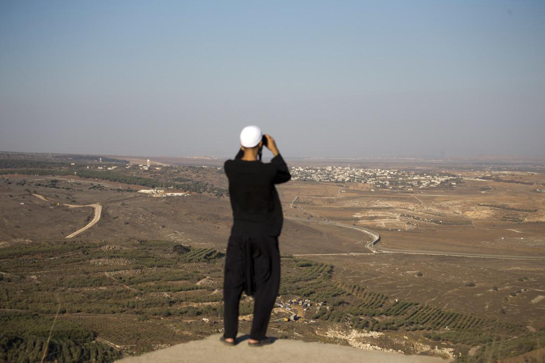 Un druso osserva il villaggio siriano di Jubata al-Khashab dalle Alture del golan, occupate da Israele nel 1967