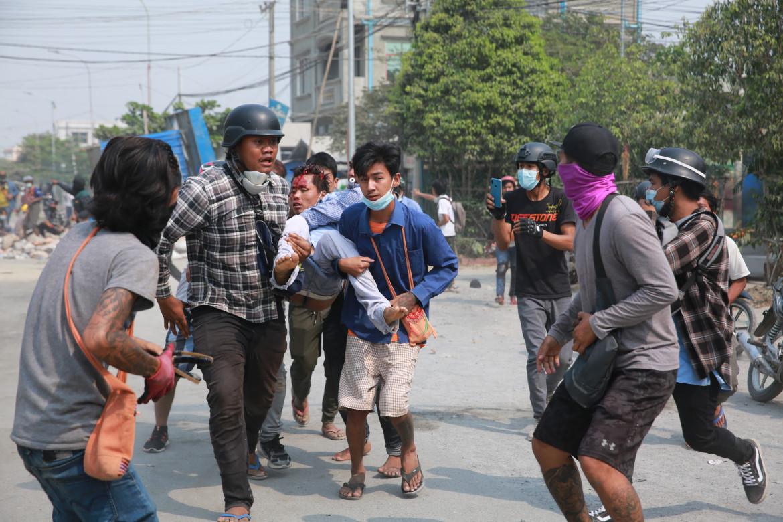 Manifestanti soccorrono un ferito in Myanmar