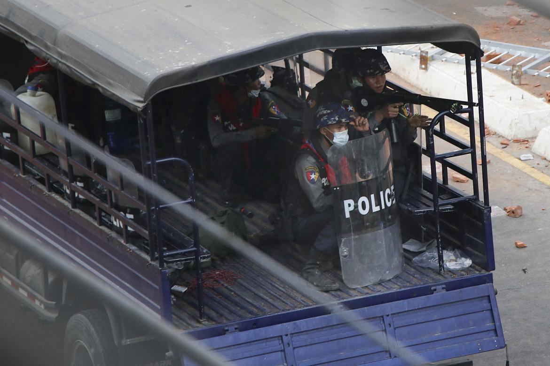 Poliziotti birmani con i fucili puntati di fronte a una barricata a Yangon