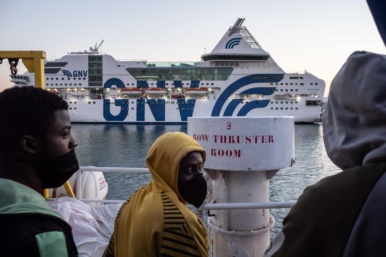 Dal ponte della Sea-Watch 3 alcuni migranti guardano la nave quarantena