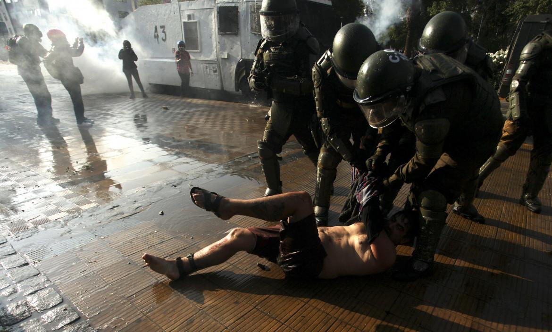Santiago, 6 febbraio 2021. Un dimostrante arrestato durante le proteste per l'uccisione di un artista di strada da parte delle forze di sicurezza nella città di Panguipulli