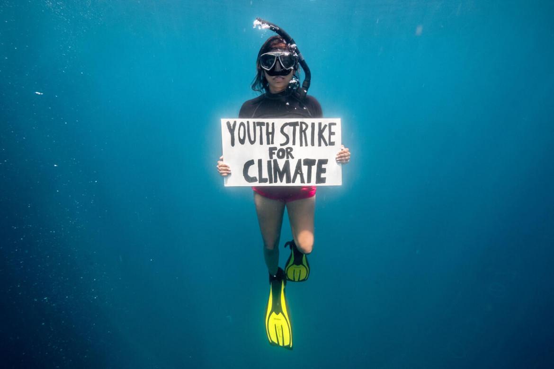 Sopra la protesta sott'acqua di un'attivista  di Greepeace nel Pacifico
