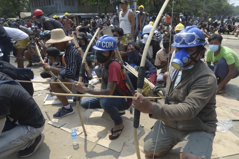 Manifestanti armati di arco e frecce ieri in piazza a Yangon