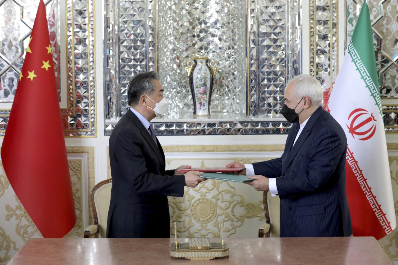 La stretta di mano tra il capo della diplomazia di Tehran, Mohammad Javad Zarif, e il ministro degli esteri cinese, Wang Yi,
