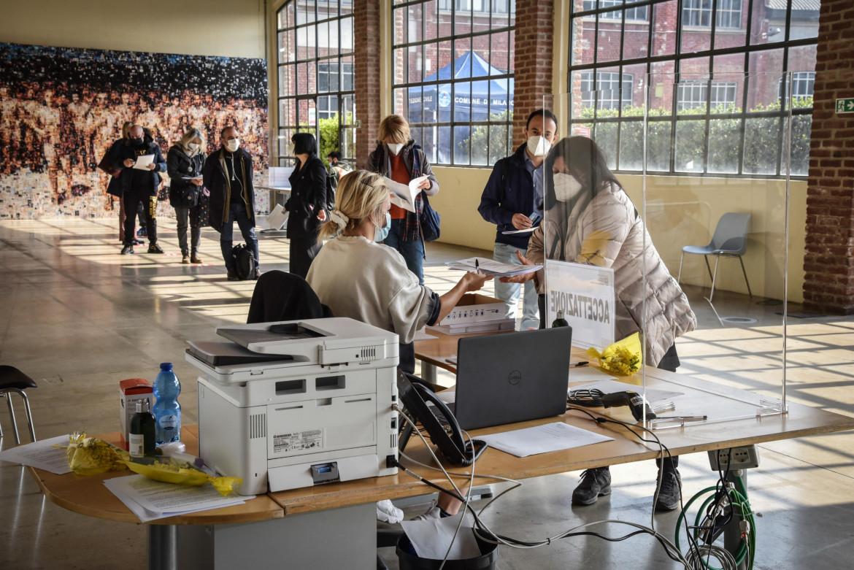 Milano, vaccini al personale scolastico alla Fabbrica del Vapore; in basso il presidente del Consiglio, Mario Draghi, durante il videomessaggio