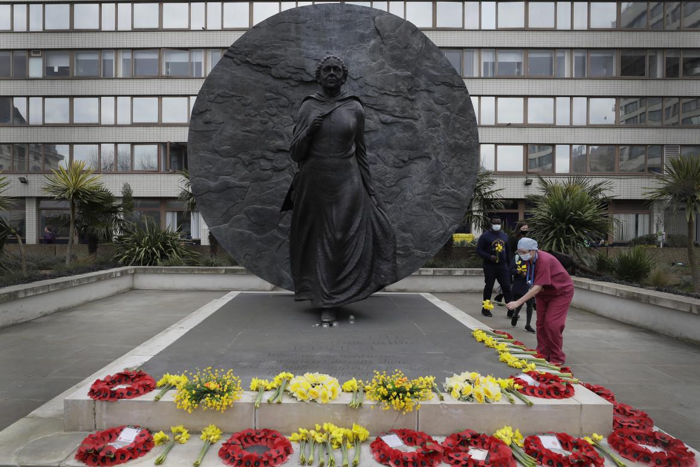 Personale dell'Nhs sotto la statua di Mary Seacole per la giornata in ricordo delle vittime del Covid