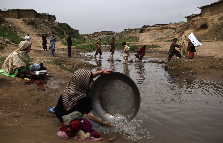 Un fiume inquinato vicino Islamabad, Pakistan, nel testo Katmandu, in fila per l'acqua potabile