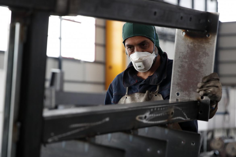 Un lavoratore con la mascherina in una fabbrica a Milano
