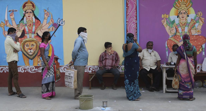 In fila per la distribuzione gratuita di riso nella città indiana di Hyderabad